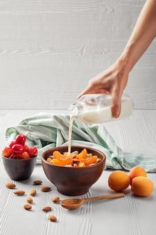Vrouwelijke hand gietende melk in muesli met abrikozen en amandelen