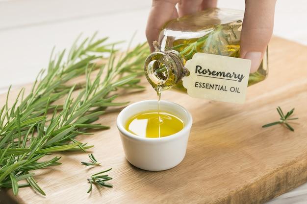 Vrouwelijke hand gietende rozemarijnetherische olie