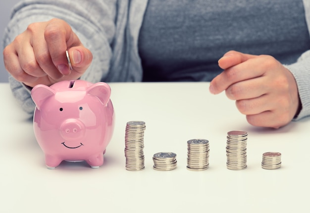 Vrouwelijke hand gooit een munt in een roze spaarvarken op een witte tafel. concept van het verzamelen van contant geld, sparen, subsidies ontvangen