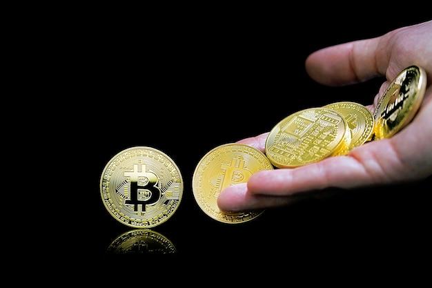 Vrouwelijke hand gooit gouden bitcoin. bitcoins. bitcoins en nieuw virtueel geldconcept. bitcoin is een nieuwe valuta.