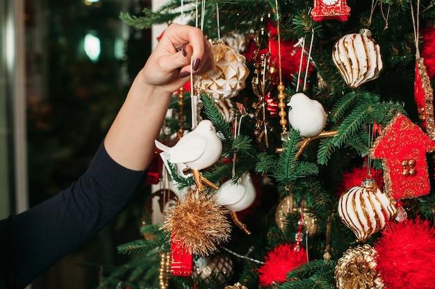 Vrouwelijke hand hangen speelgoed op kerstboom