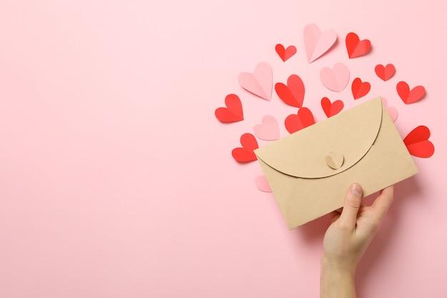 Vrouwelijke hand houden envelop op roze achtergrond met decoratieve harten