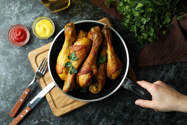 Vrouwelijke hand houden koekenpan met gebraden kip drumsticks