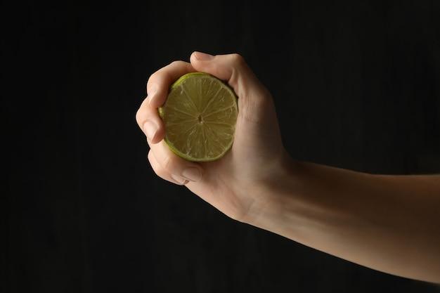 Vrouwelijke hand houden rijpe limoen op zwarte achtergrond