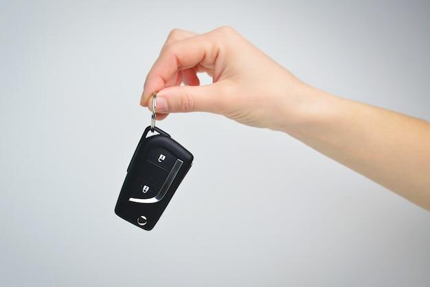 Vrouwelijke hand houdt autosleutels op grijze achtergrond een auto-afstandsbediening vergrendelen en ontgrendelen