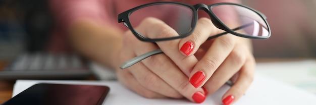 Vrouwelijke hand houdt bril naast smartphone en pen.