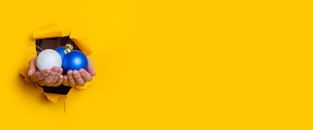 Vrouwelijke hand houdt decoratieve kerstballen in het gat op een gele achtergrond. banier.