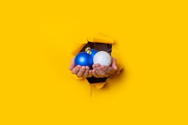 Vrouwelijke hand houdt decoratieve kerstballen in het gat op een gele achtergrond.