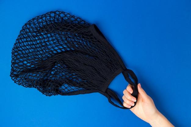 Vrouwelijke hand houdt eco string zwarte tas