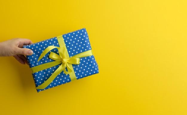Vrouwelijke hand houdt een blauwe geschenkdoos op een gele achtergrond, gelukkig verjaardagsconcept, kopieer ruimte
