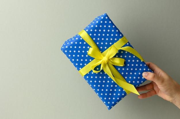 Vrouwelijke hand houdt een blauwe geschenkdoos op een grijze achtergrond, gelukkig verjaardagsconcept