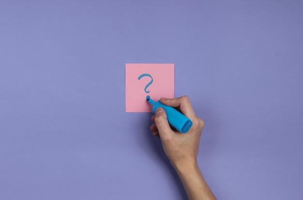 Vrouwelijke hand houdt een blauwe viltstift vast en trekt vraagtekens op memopapier