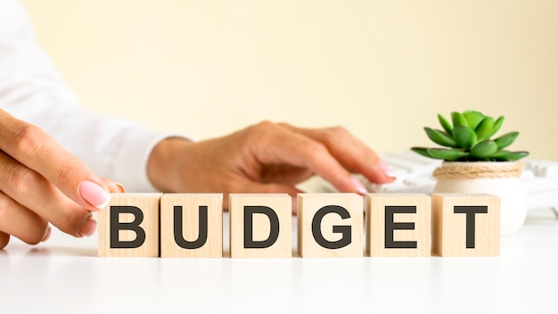 Vrouwelijke hand houdt een blok vast met de letter b van het woord budget. het woord bevindt zich op een witte kantoortafel op de achtergrond van een wit toetsenbord. financiële, marketing- en bedrijfsconcepten