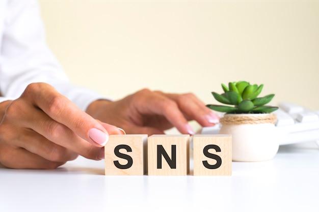 Vrouwelijke hand houdt een blok vast met de letter s van het woord sns. het woord bevindt zich op een witte kantoortafel op de achtergrond van een wit toetsenbord. sns - dienst voor sociale netwerken