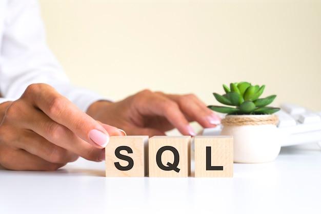 Vrouwelijke hand houdt een blok vast met de letter s van het woord sql. het woord bevindt zich op een witte kantoortafel op de achtergrond van een wit toetsenbord. sns - dienst voor sociale netwerken