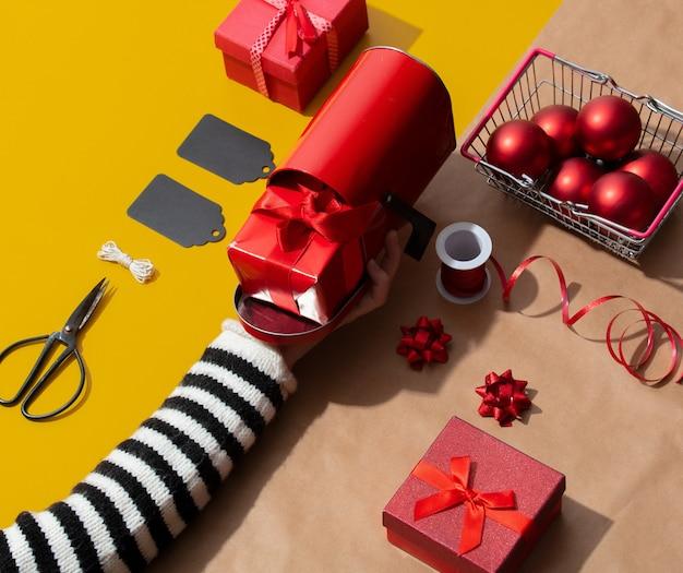 Vrouwelijke hand houdt een brievenbus in de buurt van verschillende kerst-objecten