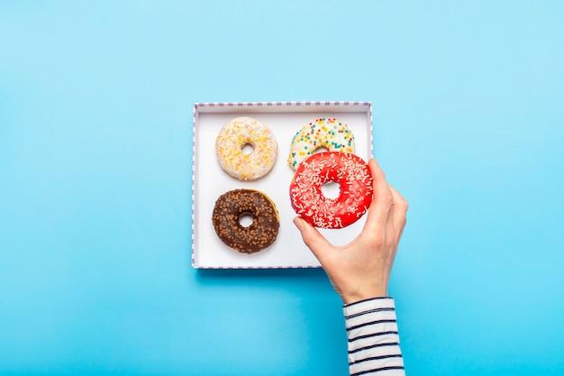 Vrouwelijke hand houdt een donut op een blauw. concept zoetwarenwinkel, gebak, coffeeshop