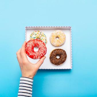 Vrouwelijke hand houdt een donut op een blauwe ruimte. concept snoepwinkel, gebak, coffeeshop. banner. plat lag, bovenaanzicht