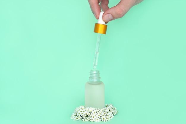 Vrouwelijke hand houdt een druppelaar uit een fles met olie. glazen container voor een cosmetisch product voor vrouwen met kleine witte bloemen op een groene achtergrond
