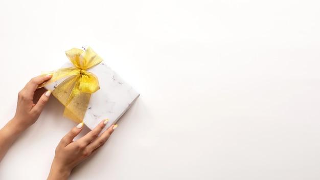 Vrouwelijke hand houdt een geschenkdoos met gouden tape