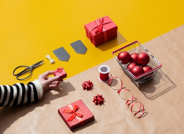 Vrouwelijke hand houdt een gfit-box in de buurt van verschillende kerstobjecten