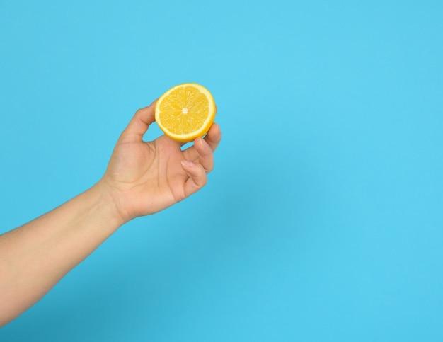 Vrouwelijke hand houdt een halve gele citroen op een blauwe achtergrond, kopieer ruimte