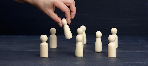 Vrouwelijke hand houdt een houten beeldje boven de menigte. het concept van het vinden van medewerkers, getalenteerde en unieke medewerkers. doorgroeimogelijkheden, keuze van een leider, banner
