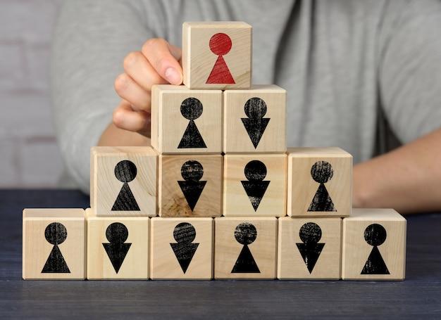 Vrouwelijke hand houdt een houten blok op een blauw oppervlak. wervingsconcept, teamwerk, effectief management. ceo zoeken, gendergelijkheid in de structuur van het bedrijf