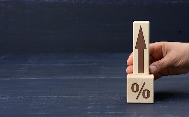 Vrouwelijke hand houdt een houten blok vast met een opwaartse pijl en een kubus met procent
