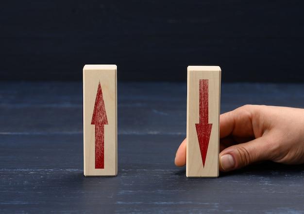 Vrouwelijke hand houdt een houten blok vast met een opwaartse pijl en een pijl omlaag. concept van toenemende winstgroei, toenemende bankrente op deposito's, blauw oppervlak