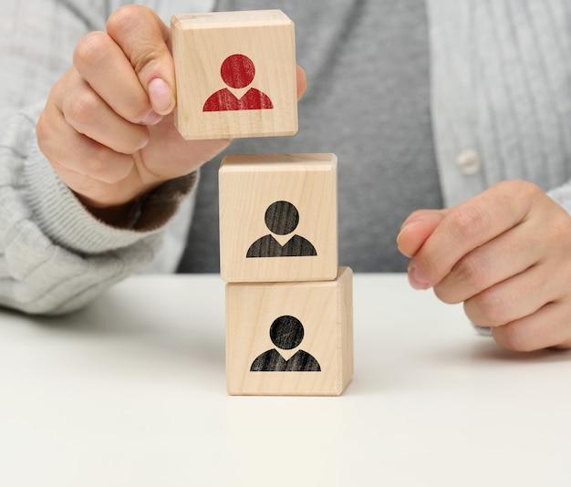 Vrouwelijke hand houdt een houten kubus vast met een man. het concept van het vinden van een leider, een getalenteerde medewerker, hiërarchie binnen het team