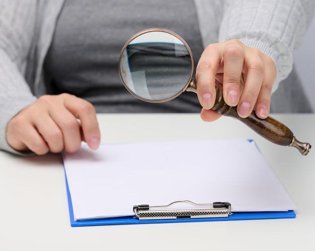 Vrouwelijke hand houdt een houten vergrootglas boven een witte tafel met documenten. zoeken naar antwoorden op vragen, bedrijfsanalyse