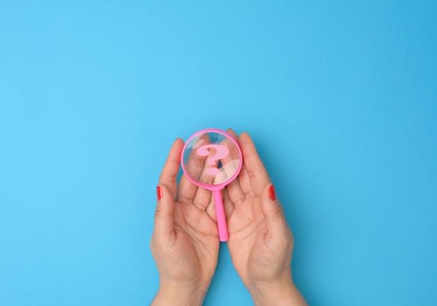 Vrouwelijke hand houdt een plastic vergrootglas en vraagtekens op een blauwe achtergrond. het concept van het vinden van een antwoord op vragen, waarheid en onzekerheid.