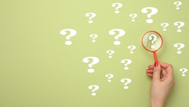 Vrouwelijke hand houdt een plastic vergrootglas en vraagtekens op een groene achtergrond. het concept van het vinden van een antwoord op vragen, waarheid en onzekerheid.