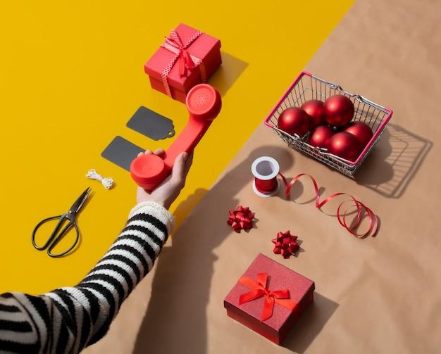 Vrouwelijke hand houdt een rode handset in de buurt van kerst-objecten