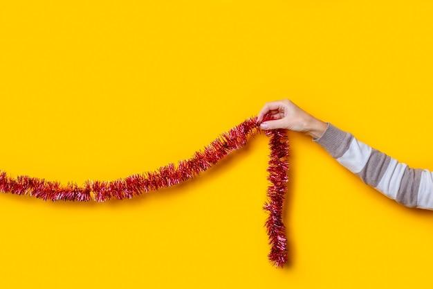 Vrouwelijke hand houdt een rode klatergouddecoratie, kerstversiering op een gele achtergrond.