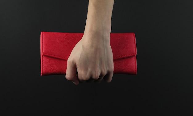 Vrouwelijke hand houdt een rode lederen tas op een zwarte achtergrond