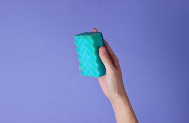 Vrouwelijke hand houdt een spons voor het afwassen op een paars