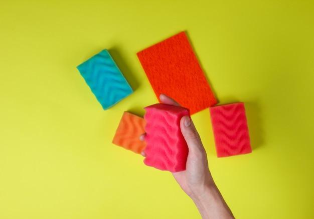 Vrouwelijke hand houdt een spons voor het afwassen op groen