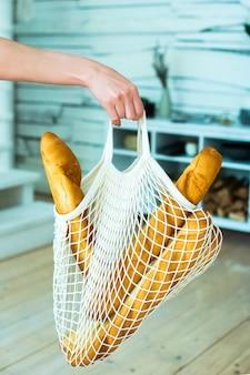 Vrouwelijke hand houdt een string bag, herbruikbaar milieuvriendelijk met stokbrood. nul afval concept. geen plastic.