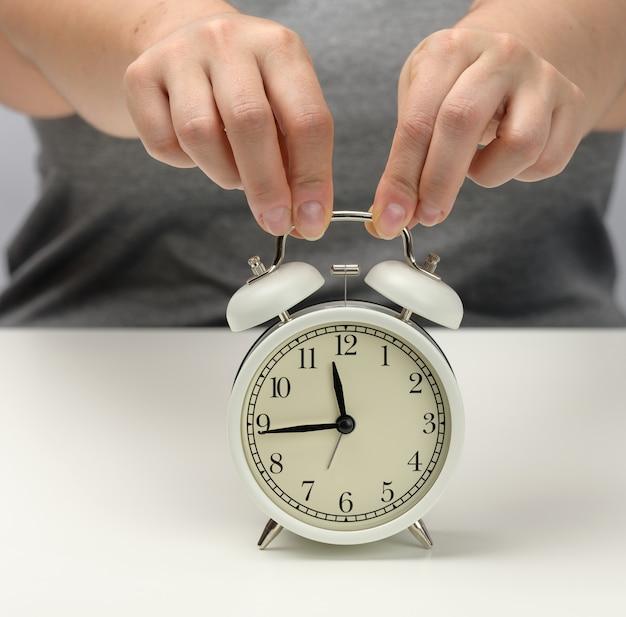 Vrouwelijke hand houdt een witmetalen wekker op een witte tafel, de tijd is vijftien voor twaalf. concept van de deadline voor de opdracht