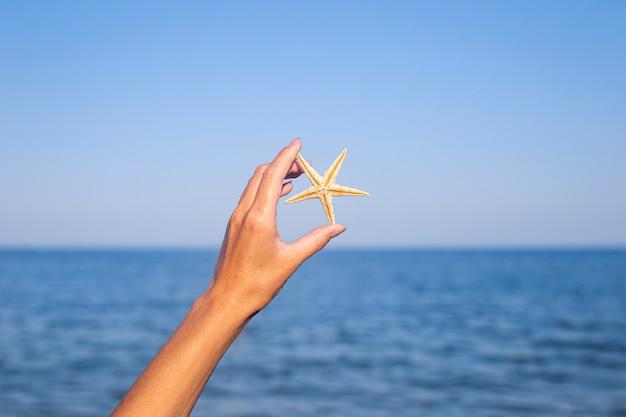 Vrouwelijke hand houdt een zeester tegen de achtergrond van de zee, de lucht.