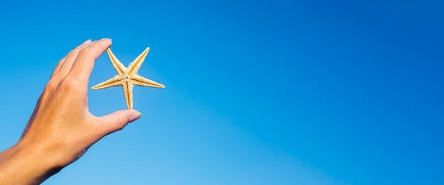 Vrouwelijke hand houdt een zeester tegen de blauwe lucht. banier.