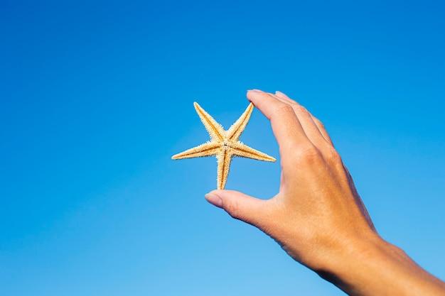 Vrouwelijke hand houdt een zeester tegen de blauwe lucht.