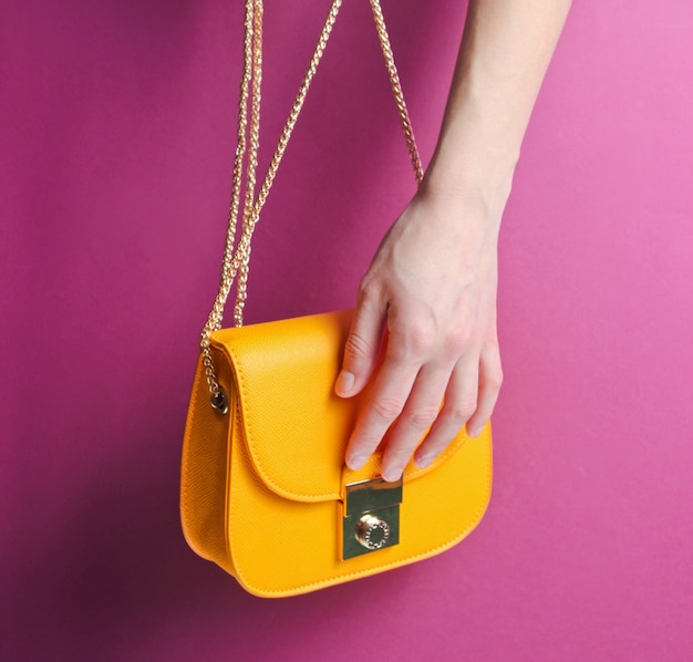 Vrouwelijke hand houdt en modieuze gele lederen tas opent met gouden ketting op paarse achtergrond.