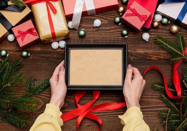 Vrouwelijke hand houdt fotolijst in de buurt met kerstcadeaus en pijnboomtakken met kerstballen op houten tafel
