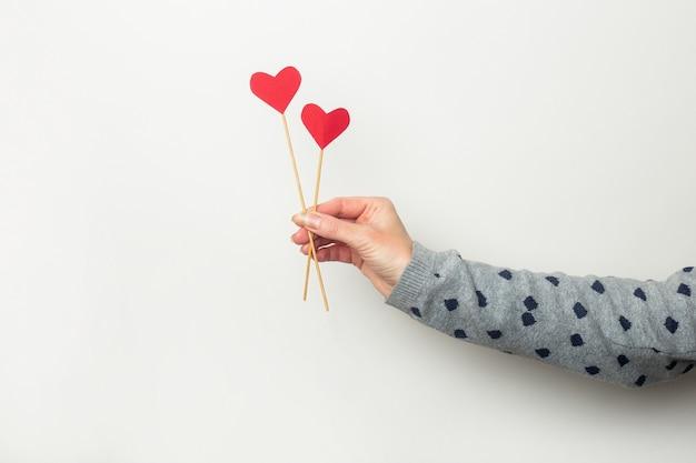 Vrouwelijke hand houdt hartjes op stokken op een lichte achtergrond. valentijnsdag, verjaardag. banner.
