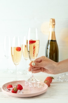Vrouwelijke hand houdt heerlijke rossini-cocktail op witte houten achtergrond