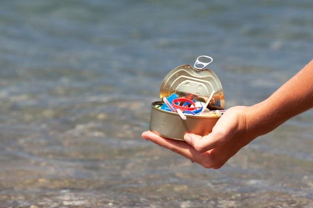 Vrouwelijke hand houdt huishoudelijk afval vast dat op het strand is verzameld en op het wateroppervlak drijft