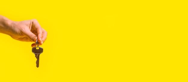 Vrouwelijke hand houdt huissleutels op een gele achtergrond. plat lag, banner